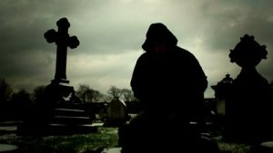 stock-footage-hooded-man-sitting-among-gravestones-silhouetted