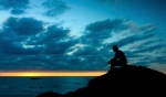 Silhouette of a man sitting down at sunset