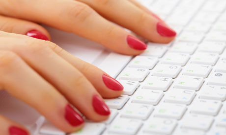 A woman's hands on a computer keyboard